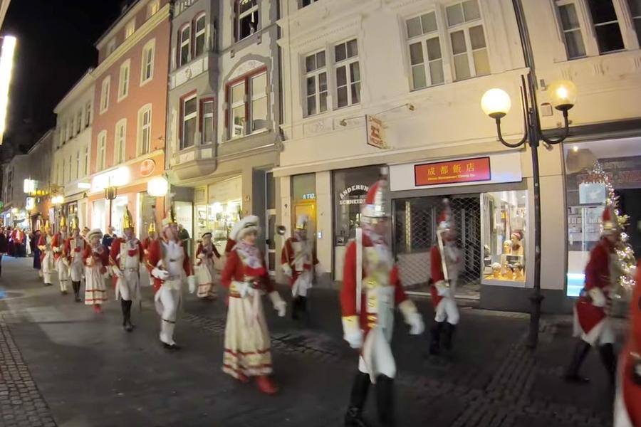 Screenshot aus dem Video der EhrenGarde des Wachhäuschenaufstellfestes der Kavallerie 2020: Die Ehrengardisten ziehen marschierend durch die nächtliche Friedrichstraße. Durch das Klicken wird das Video abgespielt.